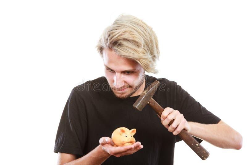 Mann ungefähr, zum von Sparschwein mit Hammer zu brechen lizenzfreie stockfotos
