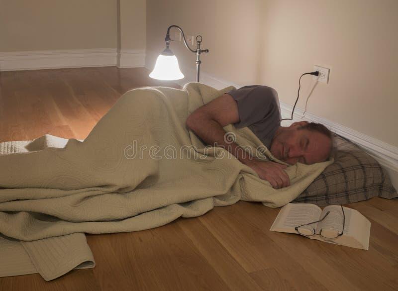 Mann unter Decke auf Boden lizenzfreie stockbilder