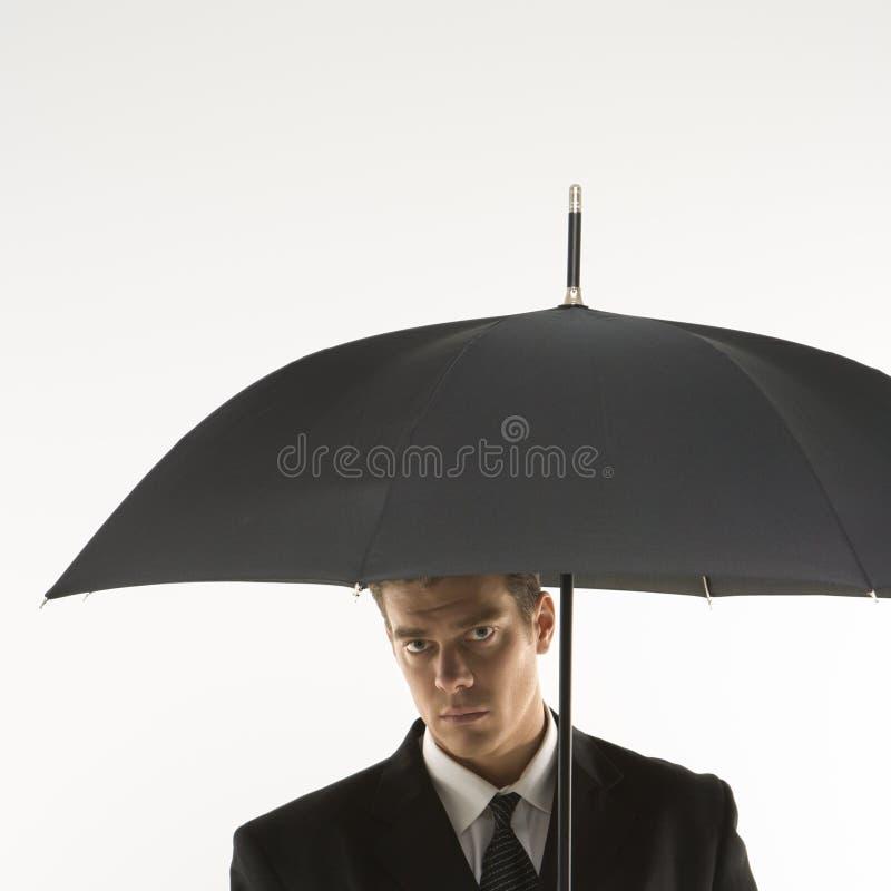 Mann unter Regenschirm. stockbild