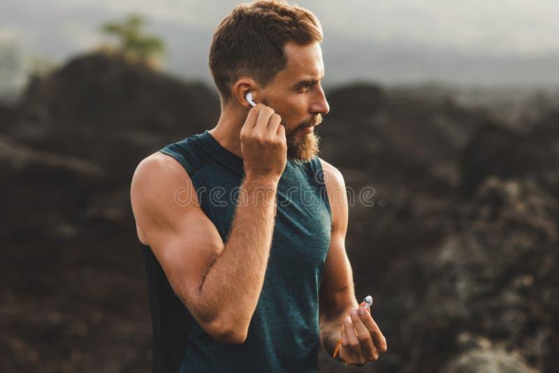 Mann unter Verwendung der drahtlosen Kopfhörer lüften Hülsen auf dem Laufen stockfotos