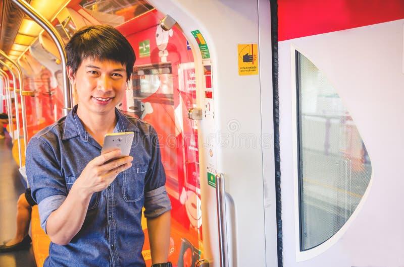 Mann unter Verwendung der simsenden Mitteilung des Smartphone im U-Bahn- oder Himmelzug, gehend, am Sonnenaufgangmorgen zu arbeit lizenzfreie stockfotos