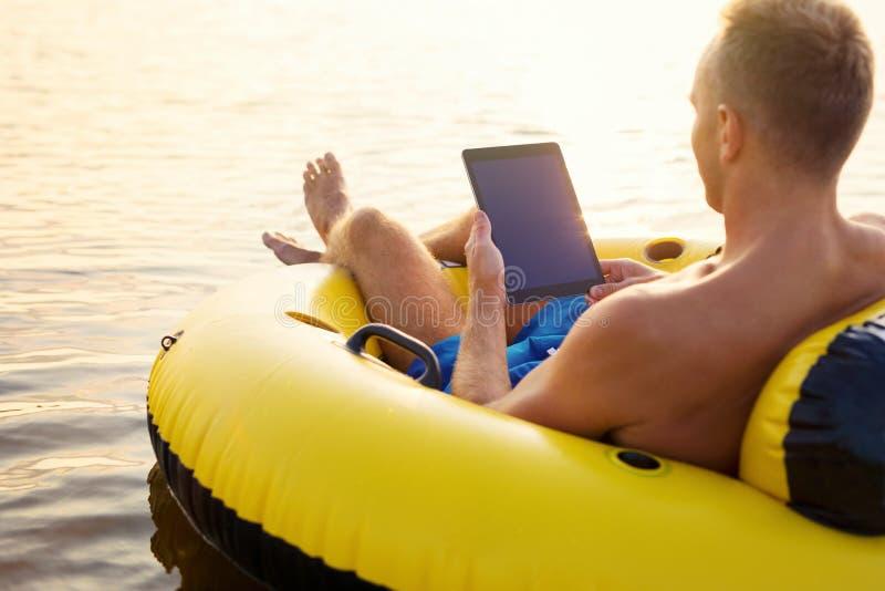 Mann unter Verwendung der Tablette bei der Entspannung im Wasser lizenzfreie stockfotografie