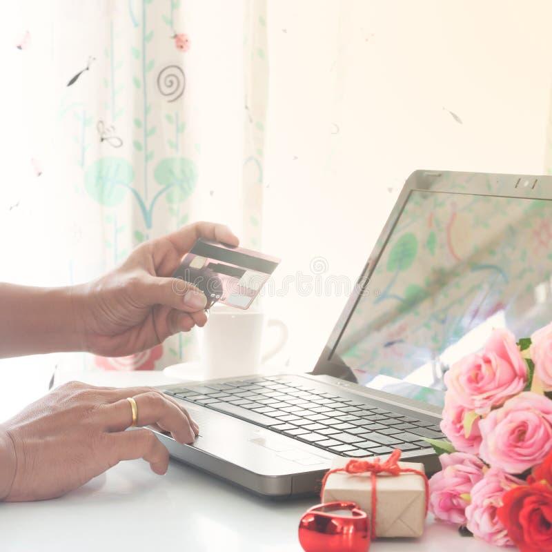 Mann unter Verwendung des Computers und Kreditkarte mit Geschenk und Rosen auf der Tabelle, online kaufend valentines lizenzfreie stockfotos
