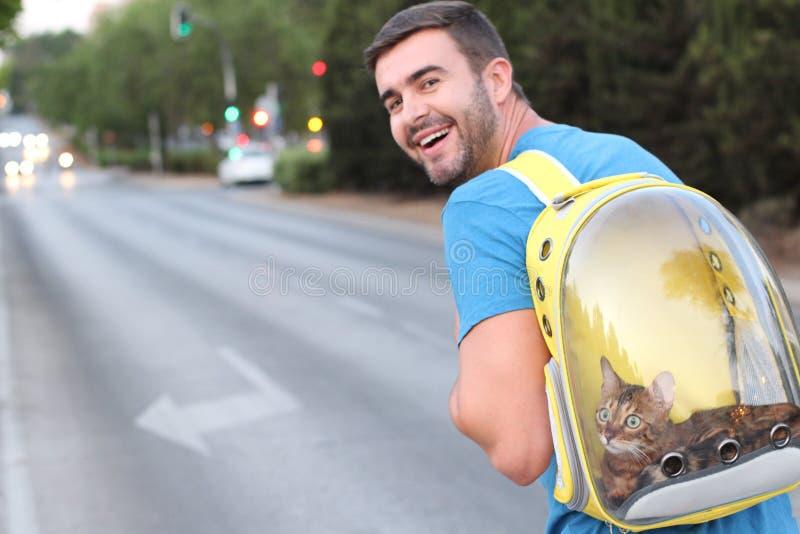 Mann unter Verwendung des Rucksacks mit einer Öffnung für sein Haustier lizenzfreie stockfotos