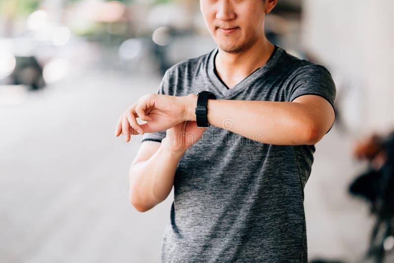 Mann unter Verwendung des smartwatch beim Rütteln stockfoto