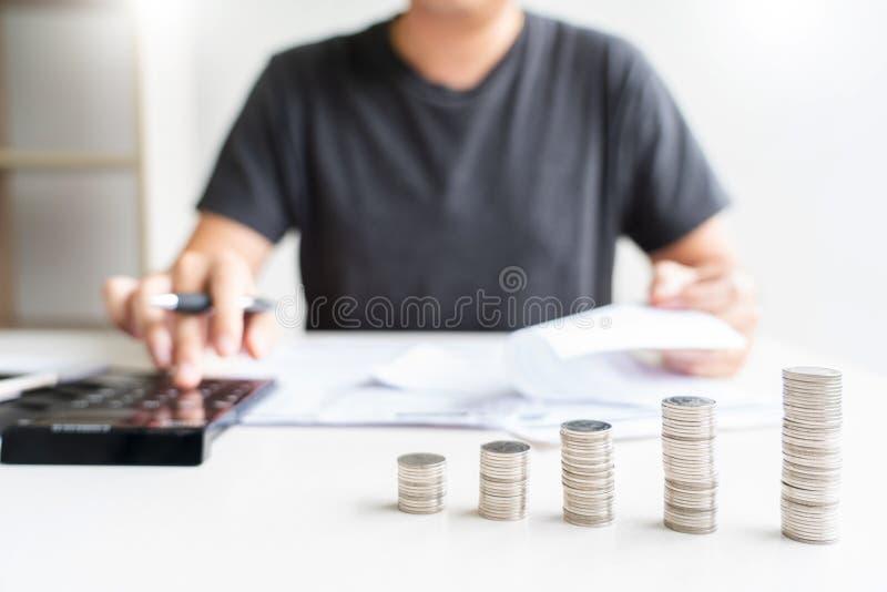 Mann unter Verwendung des Taschenrechners und Rechnungen zu berechnen quittieren in den Hauptausgabenzahlungskosten mit Papieranm stockfotografie