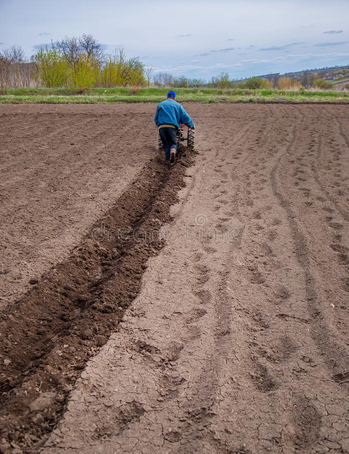 Mann unter Verwendung eines Landwirts auf einem Gebiet auf einem Bauernhof, bevor Kartoffeln gepflanzt werden stockfoto