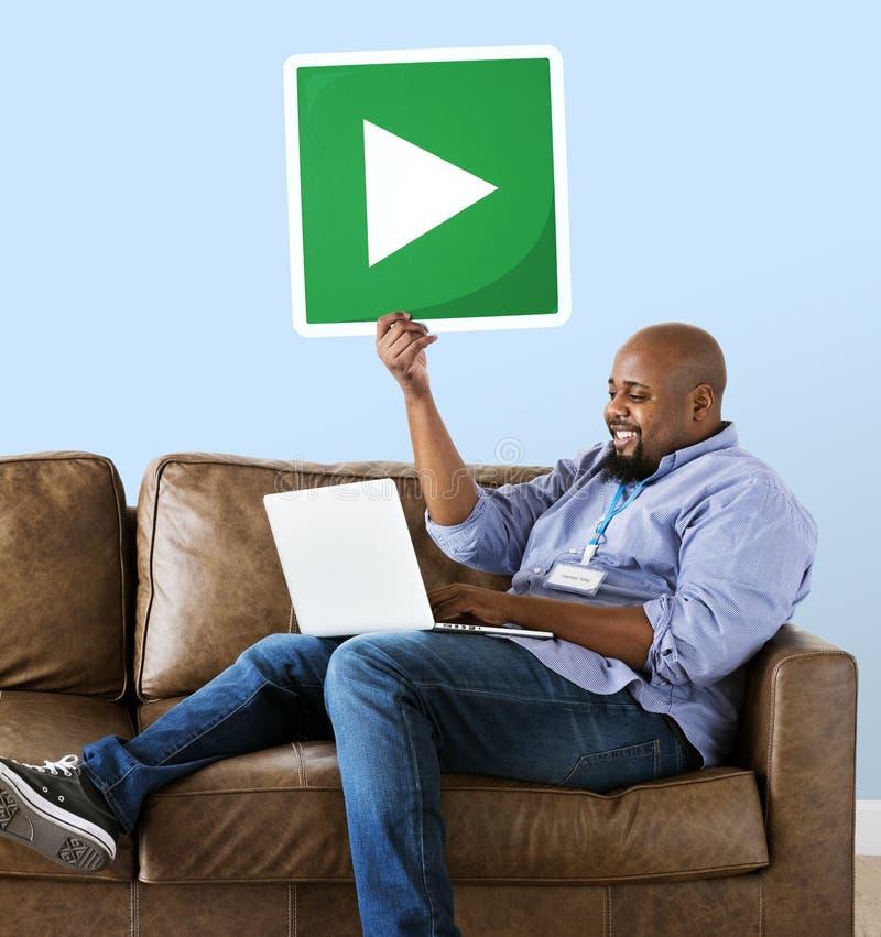 Mann unter Verwendung eines Laptops und des Haltens eines Spielknopfes lizenzfreie stockfotografie