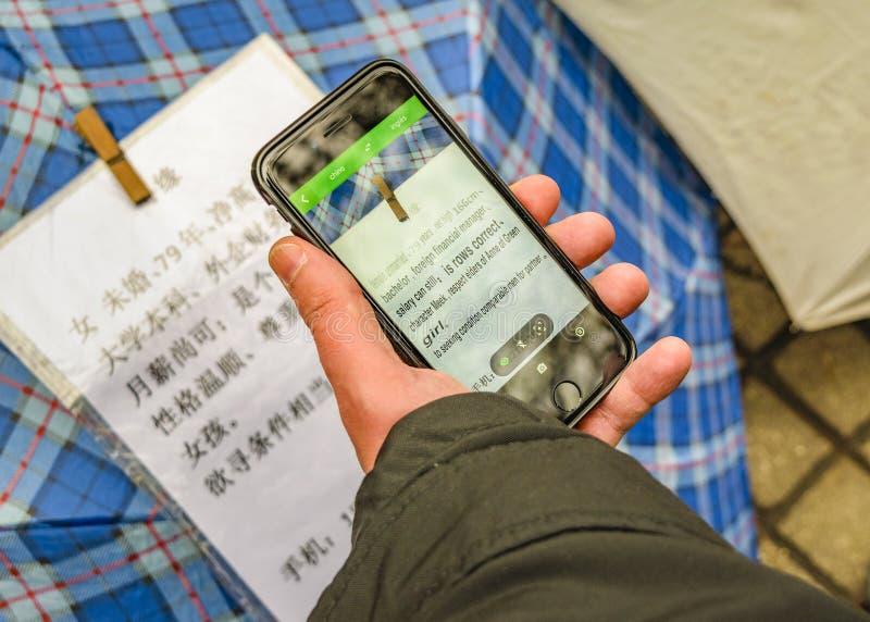 Mann unter Verwendung Googles übersetzen, um chinesische Briefe zu lesen stockbilder