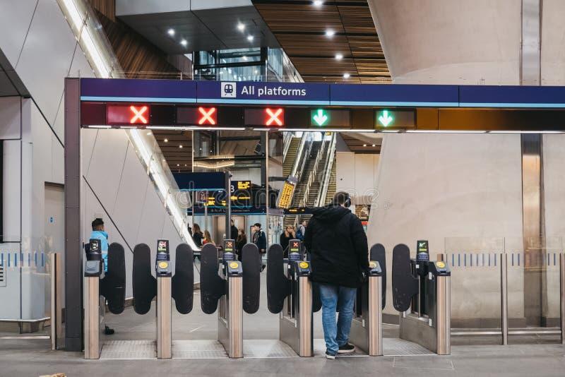 Mann unter Verwendung seiner Reisekarte auf den Eingangstoren innerhalb des London-Brückenbahnhofs, London, Großbritannien stockfoto