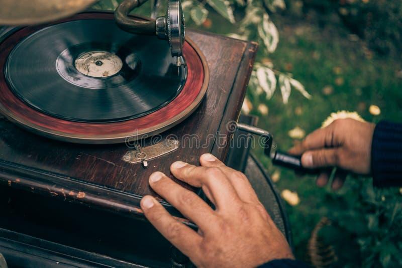 Mann verdreht einen Stift auf einem Weinlesegrammophon, um Musik, Retro- zu spielen getont stockfotos
