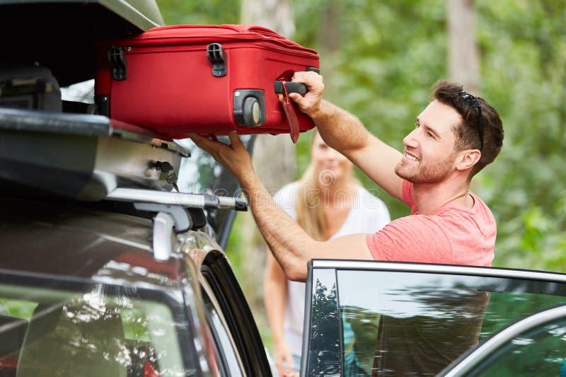 Mann verpackt Koffer im Dachkasten auf dem Auto stockbilder