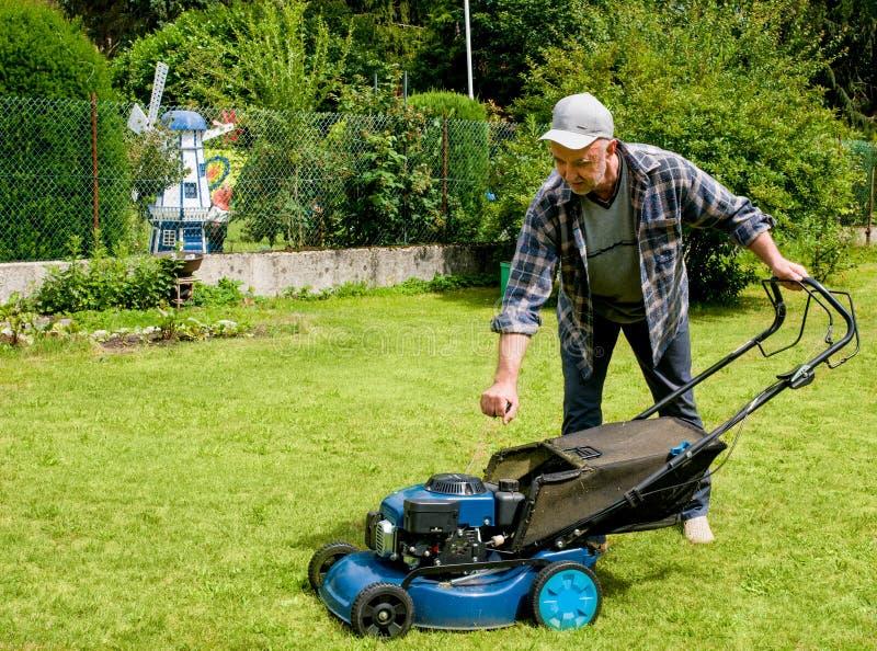 Mann von mittlerem Alter bewegt den Rasen lizenzfreie stockfotografie