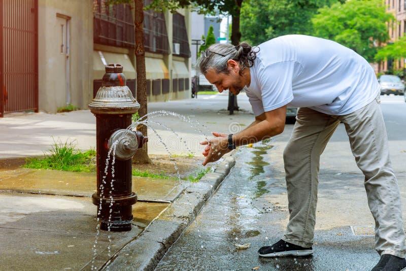 Mann von mittlerem Alter während einer starken Hitzetemperatur wird mit Hydrantwasser erneuert stockbilder