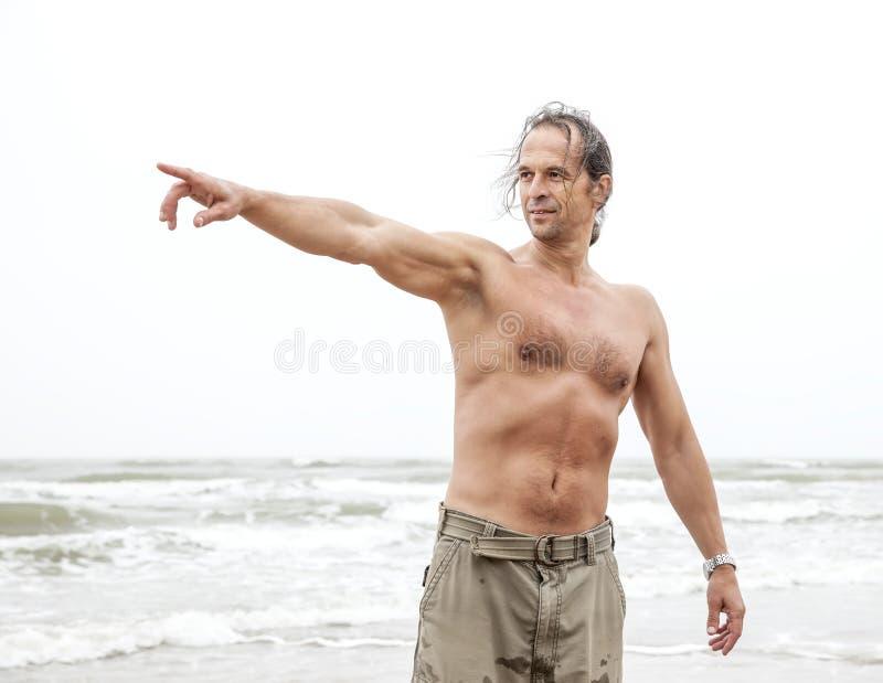 Mann von mittlerem Alter zeigt auf das etwas im Meer lizenzfreie stockfotos