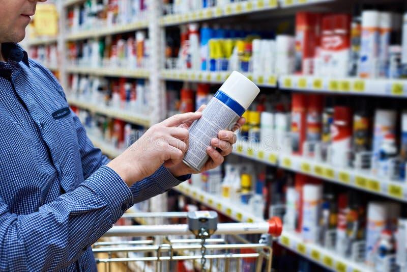 Mann wählt chemische Produkte für Auto im Speicher lizenzfreie stockfotos