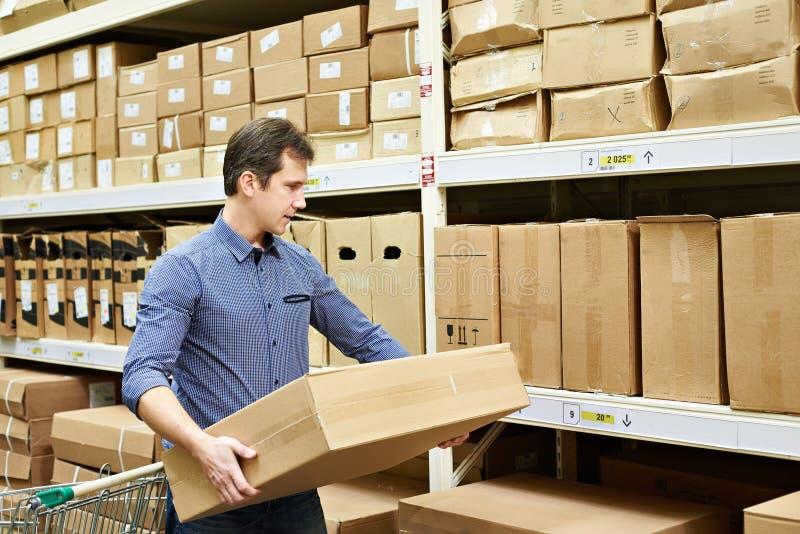 Mann wählt Kasten Waren in den Speichern lizenzfreie stockfotografie