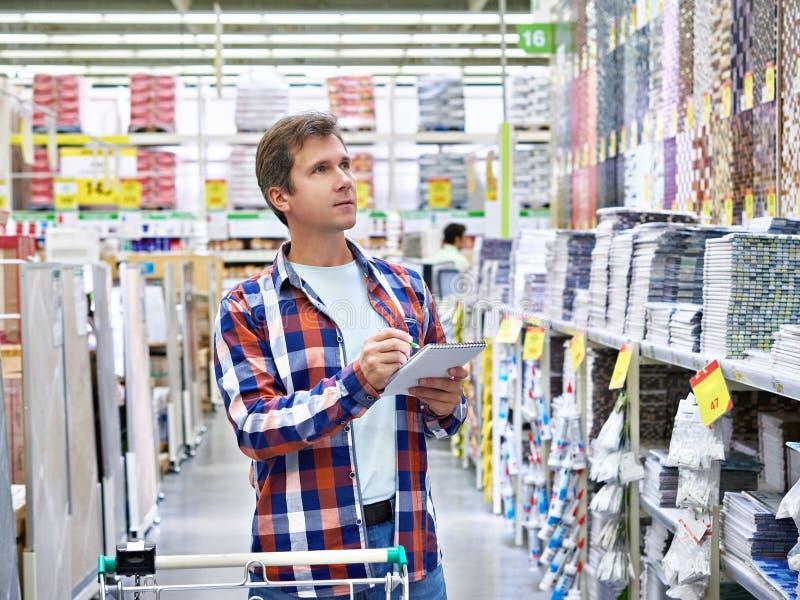 Mann wählt Wandfliesen für Badezimmer im Supermarktgebäudekameraden lizenzfreies stockbild