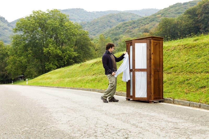Mann wählt was, zu einem Straßenkabinett zu tragen lizenzfreie stockfotos