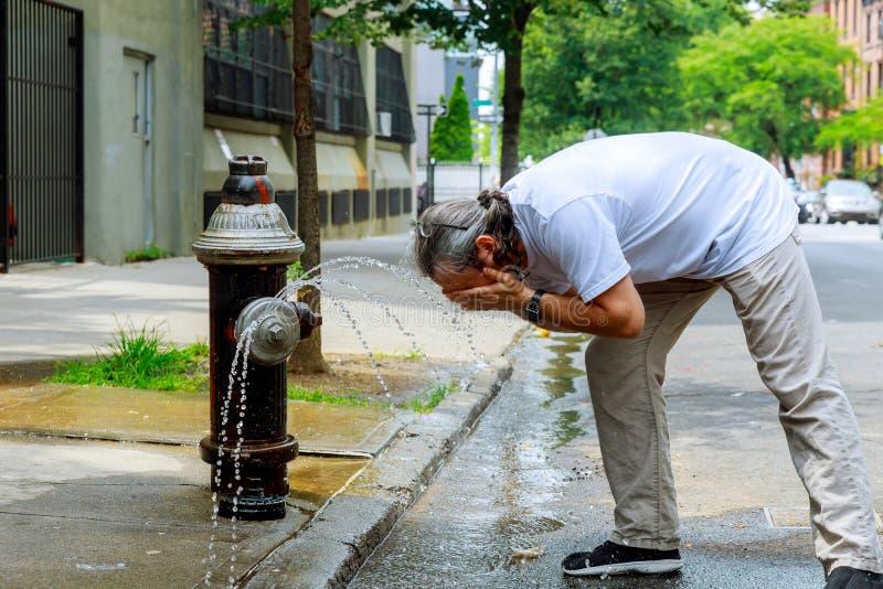 Mann während einer starken Hitzetemperatur wird mit Hydrantwasser erneuert stockfotos