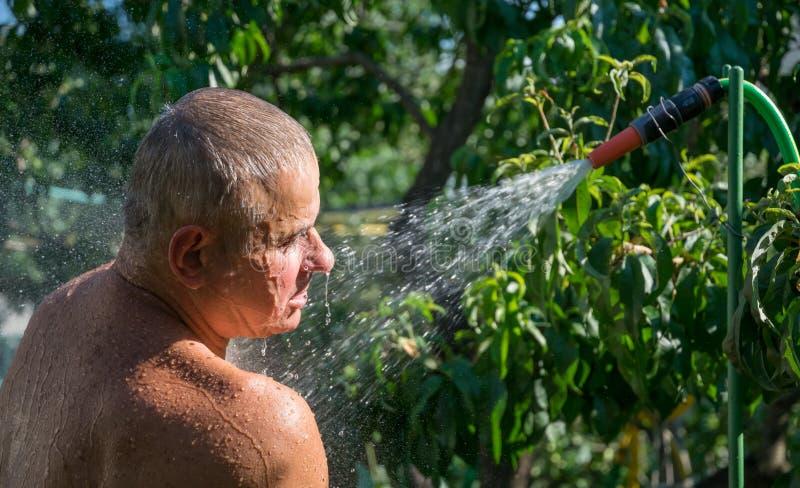 Mann wäscht sich unter dem Spray einer Sommerdusche stockbilder