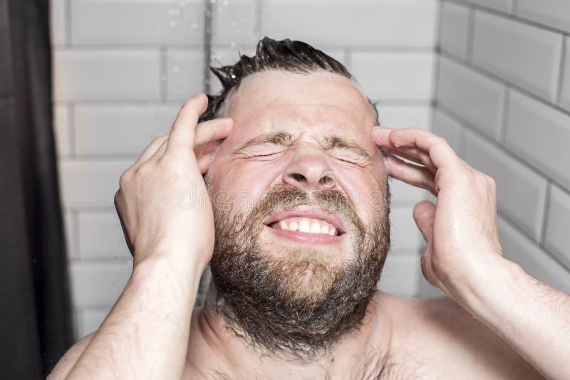 Mann wäscht weg das Shampoo vom Haar und der Schaum kam in seine Augen, die unangenehme schmerzliche Empfindungen verursachen stockfotos