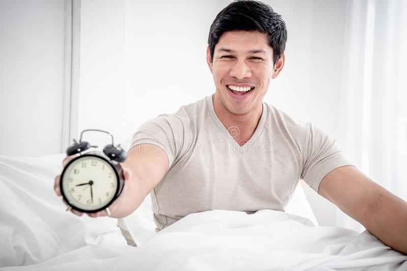 Mann wachen auf und stoppen Wecker mit optimistischem Gefühl lizenzfreies stockbild
