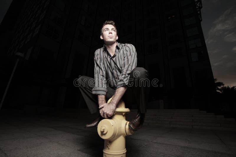 Mann warf auf einem Feuerhydranten auf stockfotos