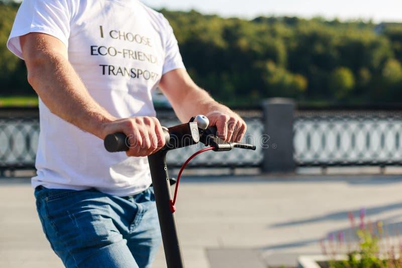 Mann in weißem T-Shirt mit Text: Ich wähle umweltfreundlichen Verkehr ist mit seinem E-Scooter nach draußen lizenzfreie stockfotografie