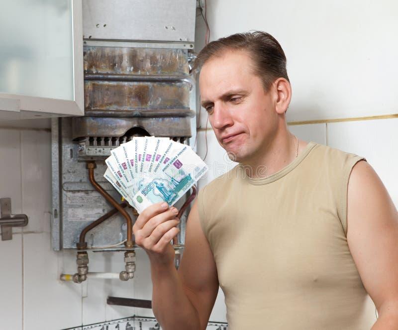 Mann zählt Geld für Reparatur eines GasWarmwasserbereiters stockfotografie