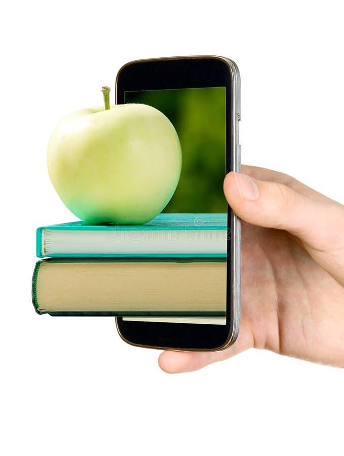 Mann zeigt Buch mit Apfel durch Handy stockbilder