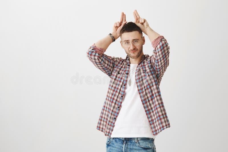 Mann zeigt seine Hartnäckigkeit Innenschuß des überzeugten attraktiven Snobs in den Gläsern, Finger hinter Kopf halten, als ob er stockfotos