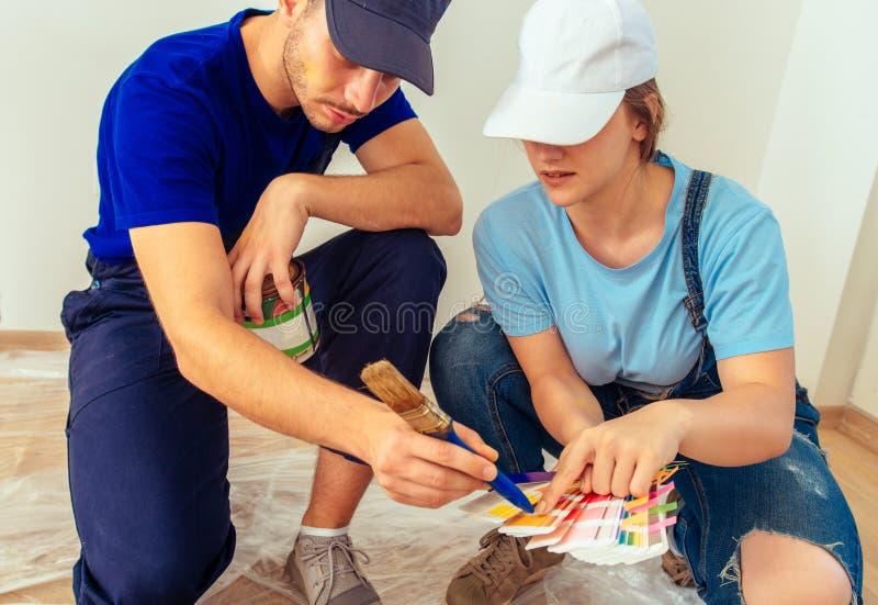 Mann zeigt seiner Freundin die rechte Farbe für Holzmöbel lizenzfreie stockfotos