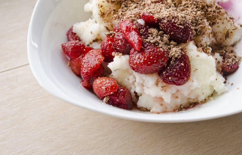 Manna pudding słuzyć z świeżej owoc truskawkami i kropiący z kraciastą czekoladą fotografia royalty free