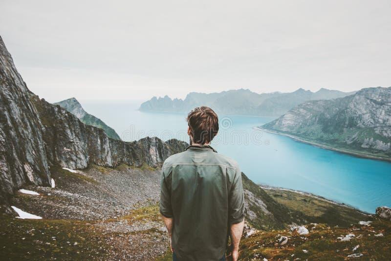 Mannabenteurer, der Fjord und Mountain View bewundert lizenzfreies stockfoto
