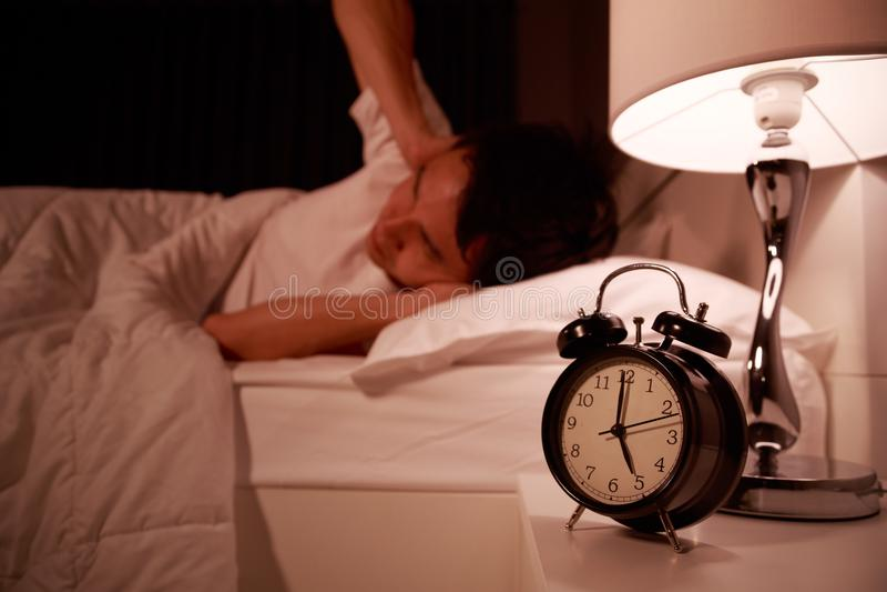 Mannabschluß seine Ohren eigenhändig von den Geräuschen des Weckers auf Bett lizenzfreie stockbilder