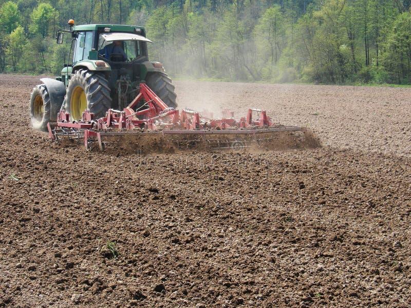 Mannarbeit mit Traktor und Egge stockbild
