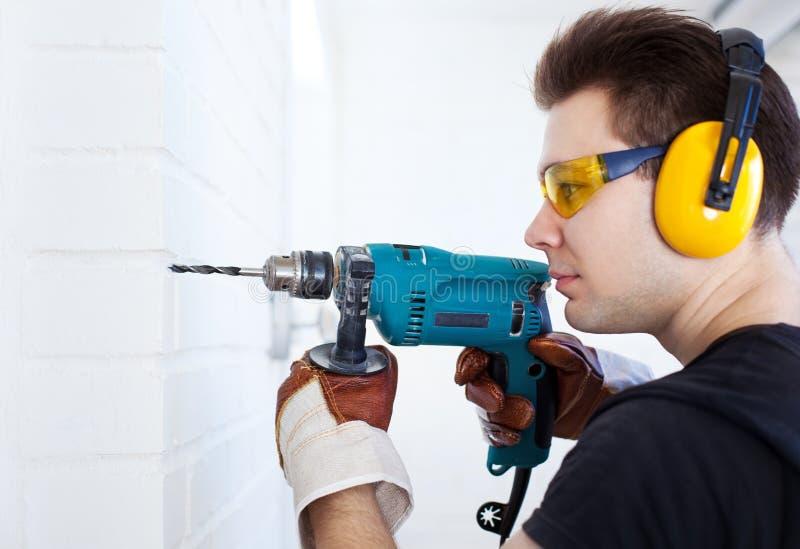 Mannarbeitskraft mit Bohrgerät stockfoto