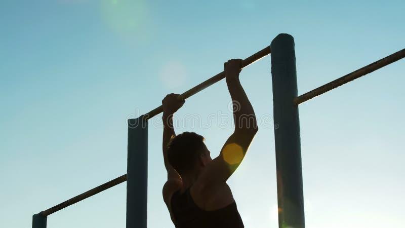 Mannathletentraining auf Kinn-obenstangen draußen, körperlicher Stärke und Sport stockbilder