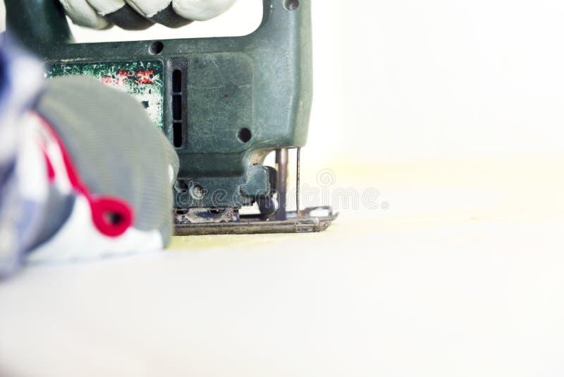 Mannausschnitt-Küche Countertop unter Verwendung der elektrischen Laubsäge Haupt-impro stockfoto