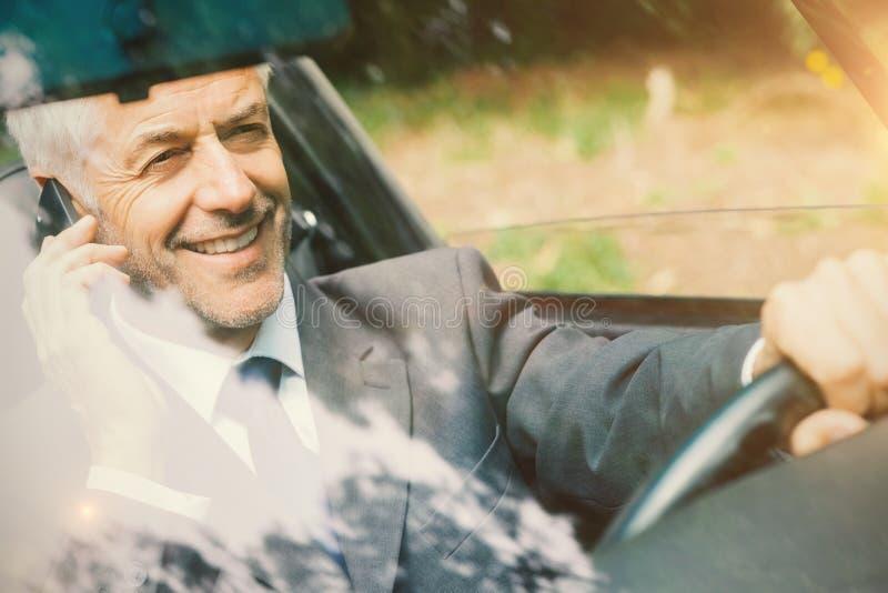 Mannautofahren mit seinem Telefon lizenzfreies stockfoto
