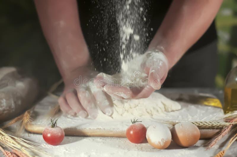 Mannbäcker übergibt knetende Butter des Rezeptmehls, Tomatenvorbereitungsteig und Herstellungsbrot lizenzfreie stockfotos