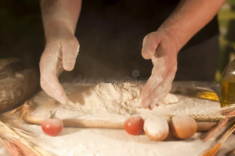 Mannbäcker übergibt mischende knetende Butter des Rezepts, Tomatenvorbereitungsteig und Herstellungsbrot lizenzfreie stockbilder