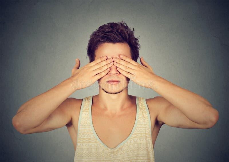 Mannbedeckungsaugen mit Handneigung sehen und verstecken sich lizenzfreie stockbilder