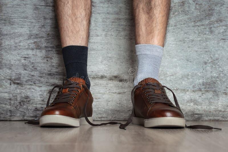 Mannbeine in den braunen Lederschuhen und verschiedene Socken auf einem dunklen Hintergrund, Abschluss oben Konzept des merkwürdi stockbilder