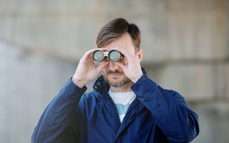 Manndetektiv passt Ferngläser auf einer Stadtstraße auf lizenzfreie stockbilder