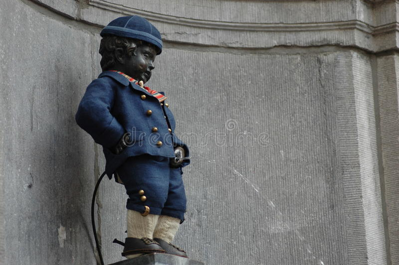 Manneken Pis in Brussels. Belgium (Little man Pee) - a landmark small bronze sculpture depicting a naked little boy urinating into a fountain's royalty free stock image