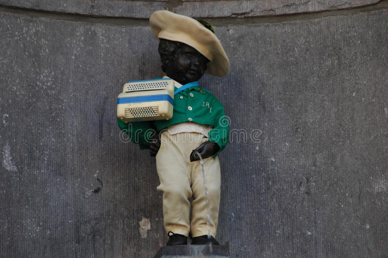 Manneken Pis in Brussels. Belgium (Little man Pee) - a landmark small bronze sculpture depicting a naked little boy urinating into a fountain's royalty free stock photography