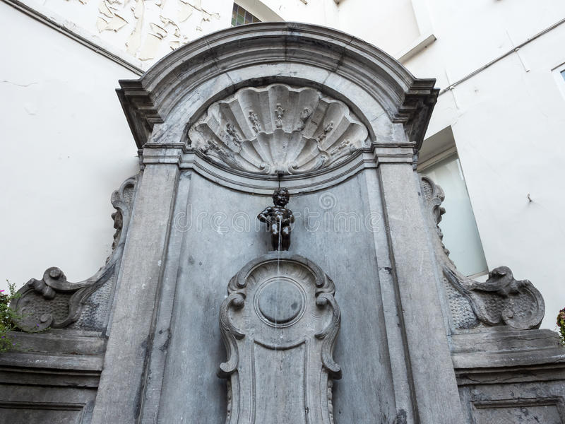 Manneken pis in Brussels, Belgium. The small ,61 cm tall, bronze statue on the corner of Rue de l'Etuve and Rue des Grands, known as Manneken Pis is symbol of royalty free stock photos