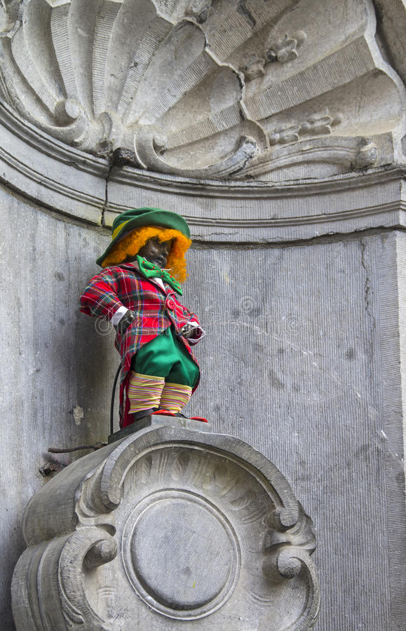 Manneken Pis dressed as a clown red. This is an old Brussels tradition to dress this statue in various funny closes royalty free stock images